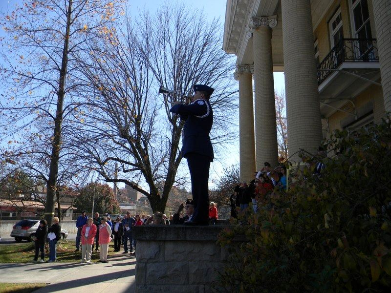 Cadet plays trumpet on balcony of Court house